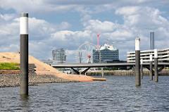 Neu eingelassene Stahldalben im Hamburger Baakenhafen - lks. Teile der neu aufgeschütteten Insel, die als Spielinsel / Freizeitinsel  in der Hafencity geplant ist.