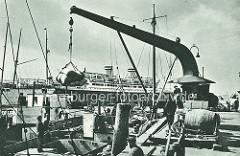 Ein Binnenschiff wird am Baumwall mit einem Kran beladen; im Hintergrund ein Passagierschiff an der Überseebrücke.