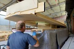 Das Deck vom Daysailer Lütje 35 wird aufgesetzt - das Zusammenfügen erfolgt mit Epoxitmasse.