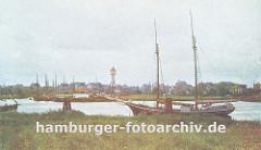 Blick über das Köhlfleet nach Finkenwerder; am Ufer liegt ein Segelschiff vor Anker, ein anderes hat den den Dalben fest gemacht. Im Hintergrund die Finkenwaerder Landungsbrücken an der eine Hafenfähre angelegt hat - zwischen den Häusern Finkenw