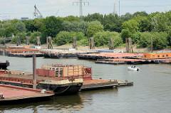 Pontons im Travehafen in Hamburg Steinwerder - ein Sportboot fährt zwischen den Arbeitsschiffen.