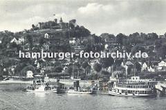 Ansicht vom alten Hamburg Blankenese - drei Ausflugsschiffe haben am Anleger festgemacht. Eine Wassertreppe führt vom Ponton zum Ufer. Auf der Spitze des Süllbergs die Türme des Restaurants.