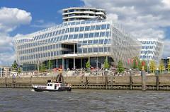 Elbseite vom Unileverhaus an der Norderelbe in der Hafencity Hamburgs - Touristen sitzen auf der Terrasse am Wasser in der Sonne, ein Sportboot fährt elbabwärts.
