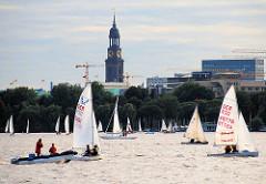 Segelboote auf der Aussenalster in Hamburg - hoch ragt der Kirchturm von der St. Michaeliskirche / Michel über den Häusern und Bäumen der Hansestadt.