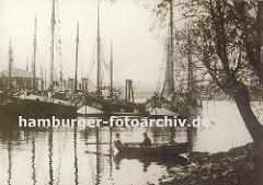 mehrere Fischkutter liegen bei den Landungsbrücken von Hamburg Finkenwerder - ein Ruderboot mit zwei Jungen an Bord liegt am Ufer. Im Hintergrund ein weiteres Ruderboot mit Kindern.