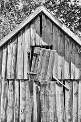 Alte Holzscheune, die Bretter und Tür hängen schief an der Fassade - Schwarz Weiss Bild.