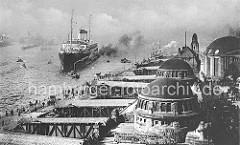 Ein Schnelldampfer der Reederei Hamburg Süd läuft im Hamburger Hafen ein . Das Passagierschiff wird von einem Schlepper zur Anlegestelle gezogen, dicker Rauch steigt aus dem Schornstein. Auf dem Ponton der Landungsbrücken warten Angehörige, die di