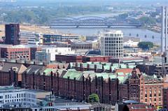 Kupferdächer der historischen Hamburger Speicherstadt und moderne Neubauten in der neuen Hafencity - im Hintergrund die Norderelbbrücken.