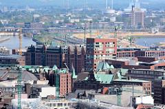 Blick über die Dächer und Giebel der Speicherstadt und Neubauten der Hafencity Hamburgs Richtung Baakenhafen; dahinter das Hotelhochhaus in Hamburg Rothenburgsort und die Müllverbrennungsanlage MVA in Hamburg Billbrook.