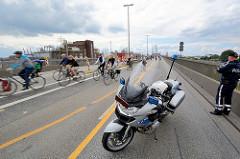 Fahrradsternfahrt in Hamburg - FahradfahrerInnen auf der Ausfahrt von der  Köhlbrandbrücke; ein Polizist mit Motorrad regelt den Fahrradverkehr.