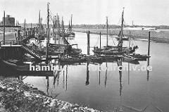 Hafenanlage von Hamburg Finkenwerder; Fischkutter liegen am Steg oder an Dalben; dazwischen kleinere Holzboote - links im Vordergrund ein offenes Festmacherboot. Vom Kai führt eine Wassertreppe zum Bootssteg hinunter.