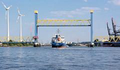Der Tanker THEODORA läuft in den Hamburger Hafen ein - die Kattwykbrücke ist hochgefahren, das Tankschiff passiert die Hubbrücke und fährt Richtung Süderelbe, Tankhafen Harburg. Rechts die Kräne beim Kraftwerk Moorburg - lks. Windräder in Hambu