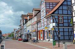 Geschäftsstrasse / Durchgangsstrasse mit historischer Bebauung - farbige Fassade, Fachwerkkonstruktion - Gewitterhimmel; Lange Strasse in Lüchow.