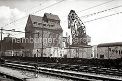 Auf den Gleisanlagen der Hafenbahn stehen Güterwaggons für den Fischtransport; dahinter am Hafenkai des Altonaer Hafen ein 40 Tonnen Doppellenker-Wippkran und der Getreidespeicher.  (ca. 1938)