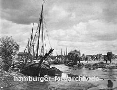das Köhlfleet in Hamburg Finkenwerder bei Ebbe - das Fleet ist fast trocken und die Frachtschiffe, Fischkutter und Schuten liegen fest im Schlick; am gegen über liegenden Ufer stehen Weiden an der Wiese.