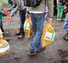 Besucher des Kartoffelmarkts tragen-ihre-kartoffelscke-vom-acker-des-biohofs-wulksfelde