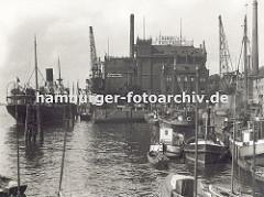 Blick auf den grossen Kohlespeicher am Hafen von Hamburg - Altona; grössere Schiffe und kleine Boote liegen am Kai oder den Dalben; im Vordergrund zwei Sport-Segelboote. (ca. 1935)