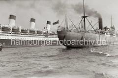 Das britische Frachtschiff PORT ADELAIDE mit Schlepperhilfe auf der Elbe - Qualm steigt aus dem Schornstein des Schiffs. Dahinter die drei markanten Schornsteine des Flaggschiffs der Hamburg Südamerika Linie, das Passagierschiff CAP ARCONA.