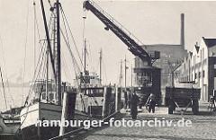 der Kai im Altonaer Hafen ist mit Kopfstein gepflastert - ein Kran holt die Ladung aus dem Laderaum des Frachtschiffs und lädt sie auf eine Anhänger der an Land steht; rechts Lagerhäuser. einige Hafenarbeiter sehen der Arbeit zu. (ca. 1939)