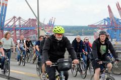 Fahrradsternfahrt in Hamburg - FahradfahrerInnen auf der Köhlbrandbrücke - im Hintergrund Containerbrücken vom Waltershofer Hafen.