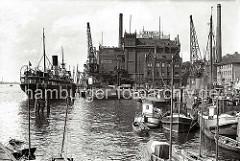 """Im Altonaer Hafen liegen die Motorschiffe und Frachtsegler am Kai -  auf der Grossen Elbstrasse steht ein Pferdefuhrwerk und wartet auf Ladung; davor eine Tankstelle mit der Aufschrift """"Essoclub"""".  (ca. 1938)"""