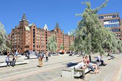 Dar-es-Salaam Platz am Magdeburger Hafen in der Hafencity Hamburgs - Touristen sitzen in der Sonne auf Bänken unter Olivenbäumen.