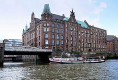 Eine Barkasse biegt auf der Tour durch die Kanäle / Fleete der Speicherstadt Hamburg in Kleine Fleth ein.