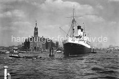 Der Passagierdampfer Monte Rosa hat an den Holzdalben in der Elbe fest gemacht. Das Schiff lief 1930 vom Stapel und wurde auf der Hamburger Werft Blohm & Voß gebaut. Eine Barkasse mit Hafenarbeitern fährt Richtung Baumwall und ein Binnenschiff bi