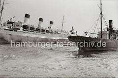 Am Passagierschiff CAP ARCONA hat eine Schute längsseits festgemacht - über das Ladegeschirr des Dampfers werden Güter an Bord gehievt. Das Frachtschiff LOTHAR mit Heimathafen Hamburg läuft in den Hafen ein.