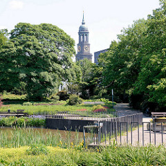 Teich in den Hamburger Wallanlagen, hohe Bäume; Kirchturm vom Michel.