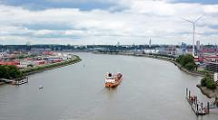 Blick auf den Köhlbrand - ein Schiff fährt Richtung Elbe; re. der Hamburger Stadtteil Steinwerder, lks. Waltershof.