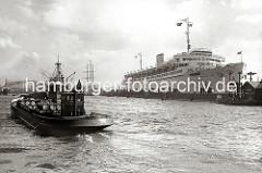 Im Vordergrund transportiert ein Hafenfahrzeug der Deutschen Vacuum Oel AG Fässer. Die WILHELM GUSTLOFF hat am Anleger fest gemacht - Arbeiter hängen auf Plattformen vor dem Bug des Schiff und streichen die Bordwand.