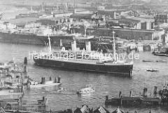 Blick auf den Hamburger Hafen - ein Passagierschiff liegt an den Dalben in der Norderelbe - eine Hafenfähre hat den Anleger am Sandtorhöft verlassen und fährt in die Elbe ein.