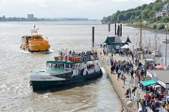 Anleger Hamburg Oevelgönne - Fahrgäste auf dem Ponton; zwei Fahrgastschiffe auf der Elbe.