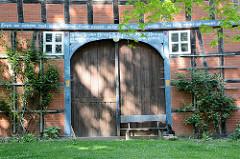 Blau einfasstes Holztor, Scheunentor mit Holzbank - Inschrift im Türbalken; Fachwerkscheune in Seedorf / Wendland.