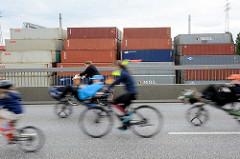 FahrradfahrerInnen bei der Fahrradsternfahrt in Hamburg - die rasante Fahrt von der Köhlbrandbrücke geht an einem Containerlager vorbei.