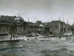 Fischkutter liegen am Anleger vor der Altonaer Fischauktionshalle - rechts das Kühlhaus, in dem der Fang bis zum Weitertransport gekühlt wird. Dahinter verläuft die Grenze von Altona und Hamburg. (ca. 1935)
