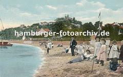 Badestrand am Elbufer von Blankenese ca. 1900; Mädchen in Kleidern stehen im Sand, andere bauen eine Sandburg. Eine Mutter liegt mit Kleid im Sand, dahinter ein Mann mit Anzug. Im Hintergrund die Häuser von Blankenese und der Süllberg.