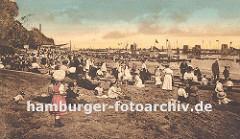 historisches Foto einer Strandszene an der Elbe bei Altona, Oevelgoenne / Neumühlen. Die Kinder sitzen in ihren Kleidern im Sand, ein Hund sieht dem Treiben zu. Frauen / Mütter mit Sonnenhüten und Kleidern und Männer mit Strohhüten oder Mützen si