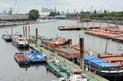 Blick über den Travehafen in Hamburg Steinwerder - Arbeitsschiffe und Schuten liegen am Ponton - im Hintergrund die Baustelle der Albphilharmonie.