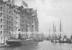Blick auf die historische Hafenarchitektur der Speicher und Lagergebäude im Hafen von Altona; ein Motor-Binnenschiff wird mit Säcken beladen, die über die Winde am Dach des Lagerhauses auf das Schiff transportiert wird. (ca. 1925)