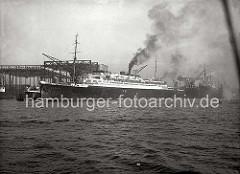Die EUROPA verlässt mit qualmenden Schornstein den Kai der Werft Blohm & Voss und startet seine Fahrt nach Bremerhaven um von dort die Jungfernfahrt nach New York zu unternehmen. Auf dem oberen Deck zwischen den beiden Schornsteinen befindet sich
