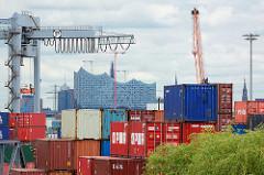 Containerstapel / Containerlager auf Hamburg Steinwerder - Kran; im Hintergrund die Fassade der Hamburger Elbphilharmonie.