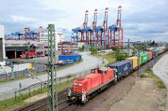 Güterzug mit Containern in Hamburg Waltershof - im Hintergrund Containerbrücken im Waltershofer Hafen.