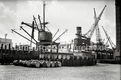 Ein Kaikran hievt Gefrierware auf das vor dem Neumühlener Kühlhaus liegende Frachtschiff. Auf den Pflastersteinen des Hafenkais liegen Metallfässer, ein Teil ist in die bereit stehenden offenen Güterwagen verladen. (ca. 1938)