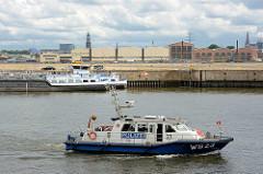 Das Schiff der Wasserschutzpolizei WS 23 fährt im Kaiser Wilhelm Hafen Patroille - dahinter liegt ein Binnenschiff am Auguste Victoria Kai - Lagerhallen und Kirchturm der St. Michaelis + Nikolaikirche.