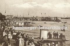 historisches Bild vom Strand an der Elbe bei Altona, Oevelgoenne. Frauen mit langen Kleidern und Hüten und Männer in Anzügen flanieren am Strand oder warten auf ein Ruderboot, das an den Verleihstationen am Elbstrand vermietet wird. Einige Ruderb