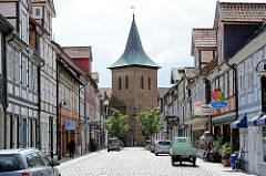 Blick durch die Kirchstrasse in Lüchow zum Kirchturm der St. Johanneskirche. Fachwerkhäuser mit Wohnungen und Geschäften.