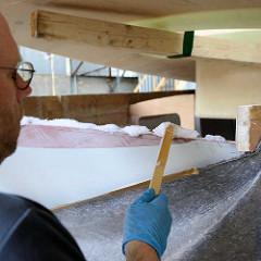 Das Deck vom Daysailer Lütje 35 wird aufgesetzt - das Zusammenfügen erfolgt mit Epoxitmasse, die auf den Schiffsrumpf aufgetragen wird.