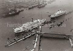 Am Anleger der Überseebrücke haben zwei Passagierschiffe festgemacht. Im Vordergrund liegen Hafenschlepper am Ponton - auf der anderen Elbseite Anlagen und Schwimmdocks der Deutschen Werft.